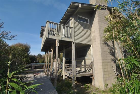 4 bedroom home on 100 x 100 lot. Upside down house with large yard and decks near the ocean.  Just 6 houses back from the beach!  Incredible potential!  Reasonable flood insurance only ~$1,800/year.