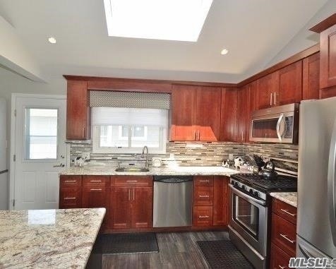Absolutely Stunning, Totally Renovated Ocean Lea Lanai Hi Ranch Has Beautiful Hi-End Chef's Kitchen And Open Layout With Cathedral Ceiling. Master Suite On Its Own Floor With Gorgeous Bathroom And Huge Walk-In Closet. Large Lower Level Den Has A Gas Fireplace. 2 Zone Central Air And Heat. Great Mid-Block Location. Just Move In...And Enjoy!