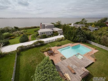 You must see this 4 bedroom, 3 bath modern. This waterfront home boasts the most spectacular sunset bay views, to be seen anywhere in the Hamptons. There is a master suite and bath, with a large private sundeck upstairs. 3 guest bedrooms, 3 baths. There is a bayfront livingroom and dining area with fireplace. The Gunite heated pool features a hot tub spa with waterfall, and is surrounded by a huge brick patio. This home has been completely updated and includes an all granite custom chef's kitchen, new roof, new heating and AC system, and more. All this on a totally private landscaped acre with plenty of room to expand on the second floor. Our Exclusive.