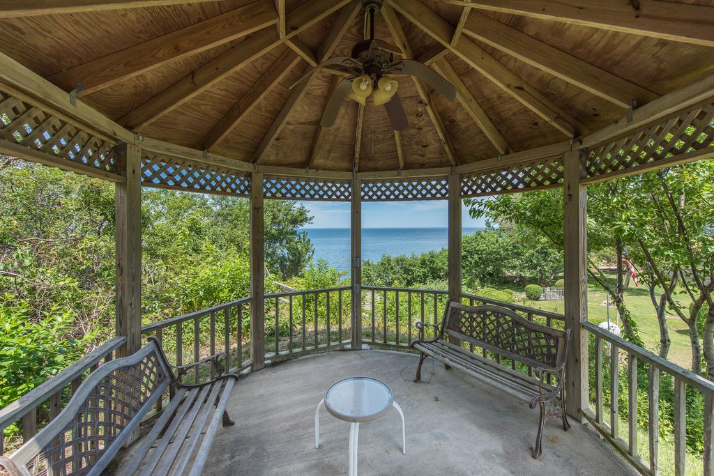 This beautiful waterfront property is situated on a bluff overlooking the Long Island Sound. This A-Frame  Home sits on 3 Acres of wooded land with a private road and beach access through a private switchback road down to the Sound. The lot includes a Cabana house, storage shed, Gazebo and covered parking and sitting areas. There are two outdoor fireplaces in addition to an indoor wood burning stove and fireplace.  The House is a unique A frame design with a loft bedroom. The entry floor has a master bedroom with en-suite bath as well as another two bedrooms and full bath with Full Kitchen and dining area. The lower walk in level can be accessed through the garage and features storage, a laundry room, half bath and unfinished bedroom/game room etc. This one of a kind property has viewpoints of the water throughout and is a private retreat in North Fork wine country.