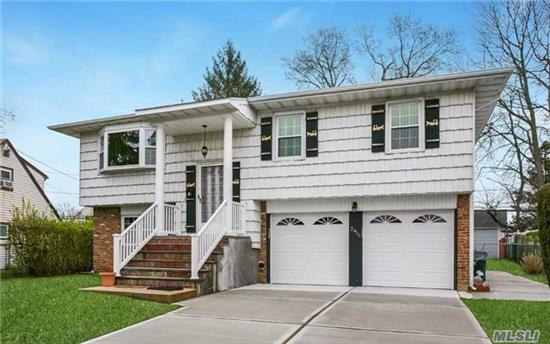 Spacious & Well Maintained 4 Bedroom, 3 Bathroom Hi Ranch Features Updated Roof, Boiler, Kitchen, Baths, Garage Doors & Exterior Stairs.