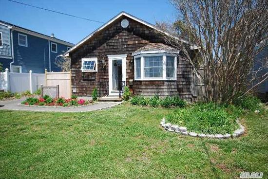 This Charming Village Bungalow Features Many Updates,  Living Room Built-Ins,  Dining Area Opens To Deck,  Wood Floors Thru Out,  Commercial Kitchen,  Large Master Bedroom And An Over-Sized Garage With Electric And Plumbing Accessed From Rear Street.  Come Watch The Boats From The Front Window....
