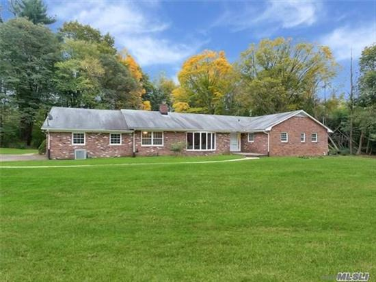 Approached by a long winding driveway, surrounded by over two acres of magnificent park-like acres, this beautifully maintained four-bedroom, three-and-a-half bath, brick ranch enjoys verdant views of sweeping level lawns and majestic trees from every one of its spacious, pristine rooms. Located in Muttontown, at the end of a cul-de-sac lane filled with equally large properties, this special home is about five-plus miles to the train station with a comfortable commute to the city. Best known for its nature preserves, magnificent estates, and pleasant residential character, the village of Muttontown boasts several country clubs that were once grand estates, as was the 550-acre Muttontown Preserve offering some of the most beautiful parkland on Long Island. Convenient to boating, beaches, golf, premier shopping, fine dining, universities, and museums, Muttontown is about 25 miles from Manhattan.  Welcoming guests with a congenial bluestone entrance foyer, the sunny and spacious floor plan includes a sunken living room with large bay window and three-sided, raised-hearth fireplace, which is shared with the formal dining room. The adjoining eat-in kitchen offers sleek white cabinetry, with planning center, granite countertops, and stainless-steel appliances, including an extra tall refrigerator and gas range, with exhaust, built into a peninsula. A service hall leads to the laundry room with sink, stainless-steel washer, dryer, and outside entrance. Ceramic tile floors flow beneath a sky-lit vaulted ceiling from the kitchen into the breakfast area that opens to the rear bluestone patio through sliding-glass doors. A bar with seating overlooks the warm and inviting sunken family room that enjoys a corner stone fireplace and French doors to the patio.  The bedroom wing, accessed from the foyer, includes a powder room, palatial master suite with luxurious master bath (whirlpool tub and separate shower,) plus three additional bedrooms and two attractive baths. The expansive