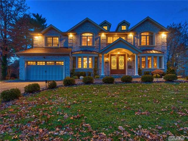 This stunning 2013 brick Colonial, with charming French elements, offers an exceptional setting for grand year-round entertaining. Every inch of its third-acre property has been masterfully landscaped and hardscaped to create an oasis of secluded enjoyment, including pool, lite basketball half-court, well-equipped outdoor kitchen with a top-of-the-line grill, ice-maker, outdoor refrigerator, and bluestone patio with a huge fire pit. Its six-bedroom, six-and-a-half bath interior is even more impressive with high-end luxury appointments throughout including a huge gourmet kitchen, lavish master suite, and a fully finished basement that, thanks to large egress windows, feels more like a first-floor entertainer's paradise. It includes a posh home theater with elevated and reclining luxury seating, a gym to rival that of a resort, billiard room and lounge, built-in bar with refrigerator and wine cooler, spa-like full bath, and more. Located in the heart in the scenic and amiable community of Roslyn Country Club, with its neatly manicured properties, towering trees and proximity to Wheatley Hills Golf Course and Clark Botanical Garden, this exceptional home has ready access to beaches, boating, fine and casual dining, the Americana Mall, and a comfortable 16-mile commute to Manhattan via rail and highway.  Entered from its wide, gabled portico through striking wood-and-iron-filigree entry doors, a two-story center-hall foyer, with grand staircase and heated, inlaid-marble floors, opens to an inviting living room and elegant formal dining room, each featuring oak floors, ornate coffered ceilings, and a bank of high casement windows. The foyer's flooring flows into an amazing and spacious gourmet kitchen offering extensive, granite-topped custom cabinetry with marble backsplash, center island with prep sink, and over-sized, high-end, integrated and stainless-steel appliances including a six-burner, two-oven gas range. A bright and airy breakfast area, with French doors to t