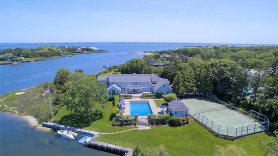 Water views from everywhere. Set on over 2 acres down a quiet Remsenburg street, this extraordinary waterfront property offers a first-floor master suite, modern kitchen with breakfast nook, waterfront living room looking out to the open bay and dining room. Room for everyone with 4 guest bedrooms and an office/possible 6th bedroom. Paver patio surrounds the oversized, heated gunite pool and leads to the pool house. Complete with an attached 2-car garage, all-weather tennis court and boat slip.