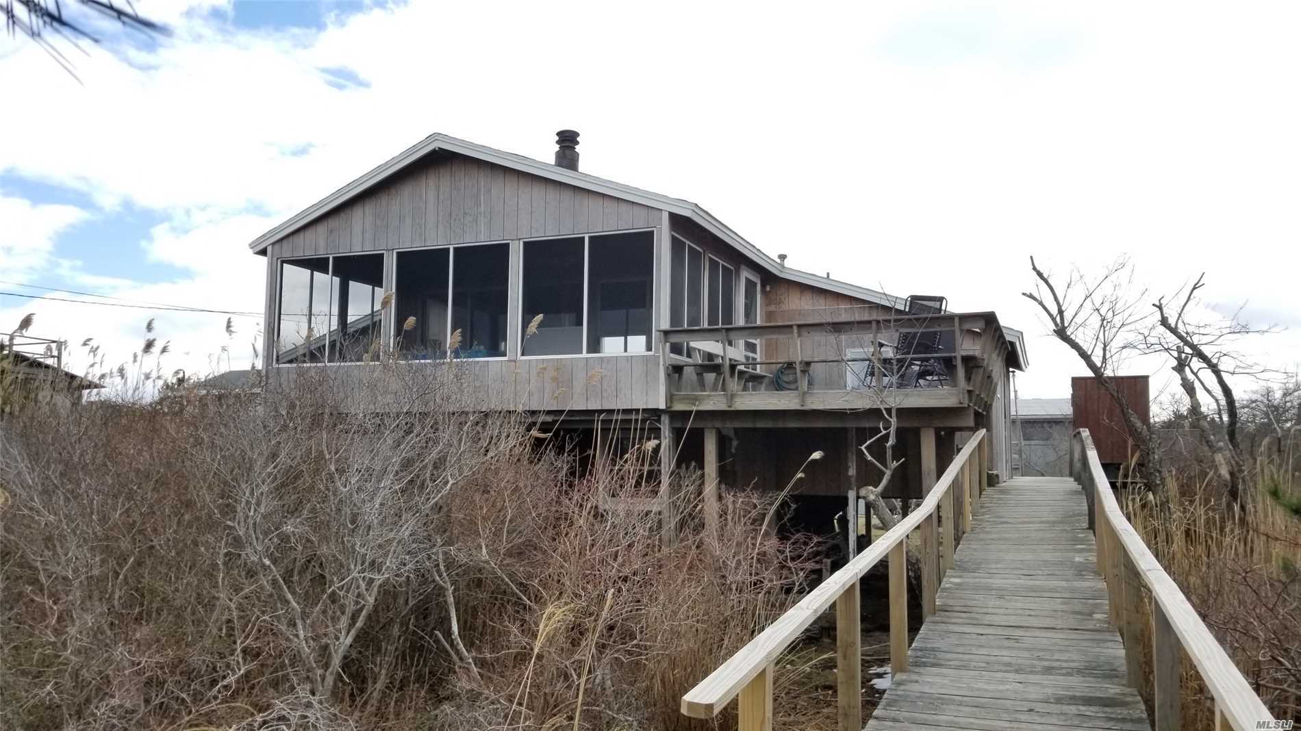 Amazing Bay Views From This Elevated Beach House. 3 Decks Plus A Large Screen Porch And Wood Burning Fireplace. Hardwood Floors Throughout. Move-In Condition. Excellent Income Potential. Short Walk To The Ocean, Bay, Ferry And Dining.