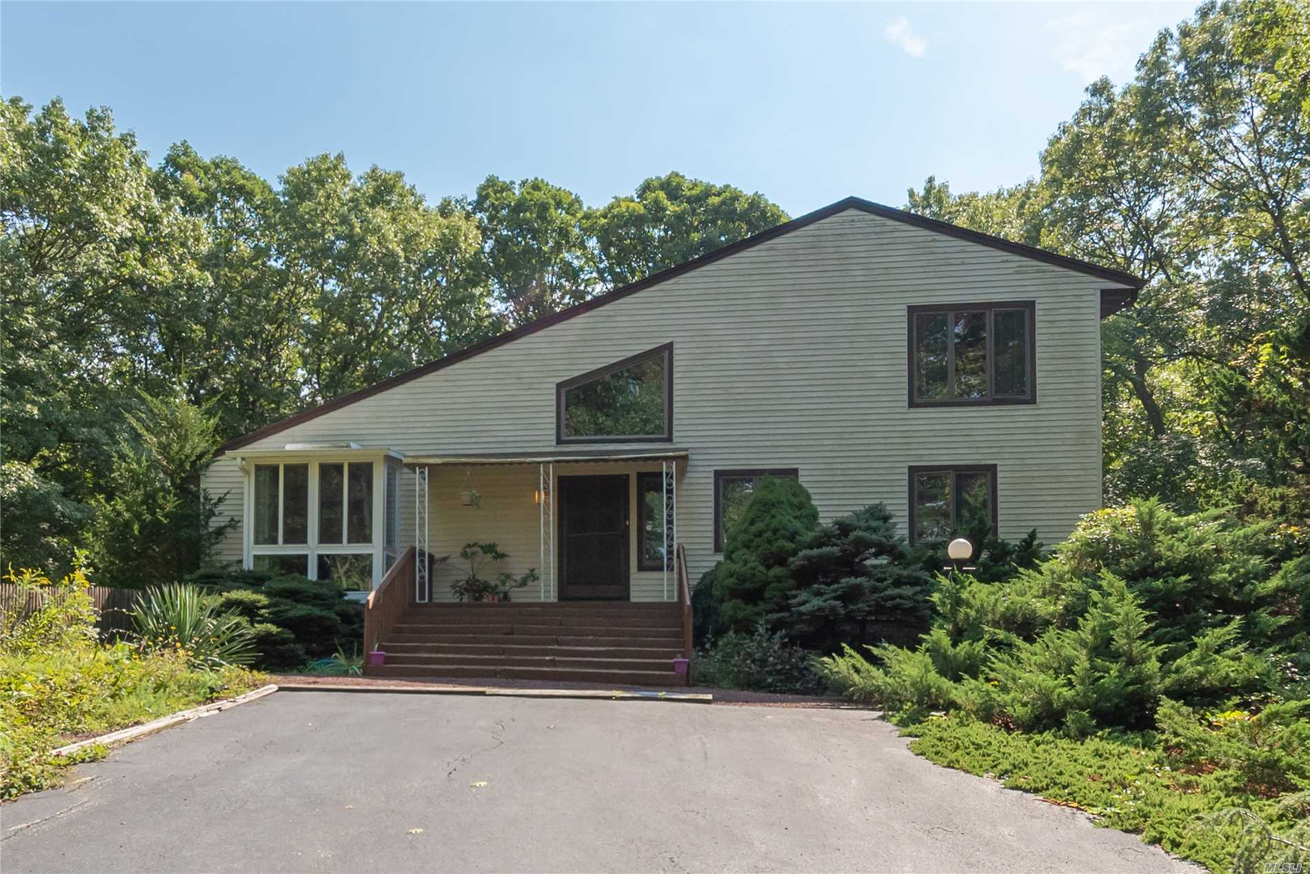 Contemporary Home In Beautiful Wooded Setting, Close To Beach And Golf Course. Open Floorplan With Cathedral Ceilings, Exposed Beams And An Open Staircase. Separate Laundry Room And Screened Porch. Full Finished Basement With .5 Bath And Outside Exit.