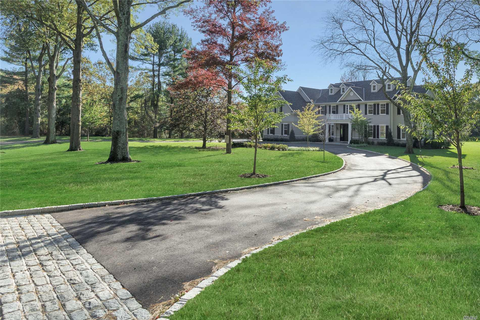 Imagine living in a brand new, state-of-the-art six-bedroom, five-and-a-half-bath home with a traditional manor-house style in a beautiful mature neighborhood of two-acre-plus homes and with only a modicum of passersby. Such is what this magnificent home offers. Standing majestically on 2.11-acres of sweeping emerald lawns dotted by towering mature trees and enfolded on three sides by walls of foliage, and approached by a long circular drive, this fabulous, newly finished Colonial has it all, including room for a possible pool and tennis court and an ideal location. Situated in the heart of Old Westbury, the home part of a section of homes that has one entrance, two cul-de-sacs, and a circular road - ideal for pleasant strolls or biking. Practically surrounded by golf courses and universities, the area is also within easy reach of major expressways for easy commuting. Long a popular area for Manhattan's magnates and luminaries, Old Westbury is just 30 minutes by railway or highway from Manhattan and Kennedy and LaGuardia airports. Conveniently located near parks and museums, it is just a short drive from fine dining, premier shopping, miles of public equestrian trails, polo club, yacht clubs and beaches.   Its traditional center-hall floor plan has been beautifully tweaked to allow easy, open flow throughout its entertaining spaces, with French doors ready to close for privacy when needed. Boasting gleaming hardwood floors, elegant crown moldings, and a myriad of windows and French doors, the first floor welcomes guests through a vestibule, with guest closets, into a spectacular two-story entrance foyer with graceful bridal staircase and stunning powder room. To the left, is the banquet-sized formal dining room in all its elegance, and to the right, a parlor is open to the inviting great room with its magnificent marble-faced gas fireplace and windows plus French doors opening to the rear property. Entered from the parlor and the living room, the spacious and sunny library/den is flooded with verdant views through many windows on three exposures. Entered from the great room and the foyer, spacious sun-drenched eat-in-kitchen offers the finest in today's finishes and appliances. Gray glass-tile backsplash accents custom oak stained walnut cabinetry with white quartzite countertops and farm sink while a large cherry center island, with prep sink and seating area, coordinates with the hardwood floors. High-send appliances include a 6-burner stainless-steel gas stove with griddle and double-oven; a side-by-side, integrated full-size refrigerator and full-size freezer; plus an integrated dishwasher; and a stainless-steel built-in microwave. A butler's pantry, accessing the dining room, provides cabinetry, similar to the kitchen, plus entry to a large walk-in pantry. Fully open to the kitchen and the great room, the sunny breakfast area overlooks the rear property through a wall of French windows and door to the patio – idea for al fresco dining. A hall off the kitchen, with back stairs, leads to the attached three-car garage, a large mudroom with many closets, including one walk-in, and a well-equipped laundry room. A nearby guest suite features a designer bath with shower and a sunny bedroom with double-closet. On the second floor, the palatial master suite enjoys its own private wing including an immense master bedroom with romantic gas fireplace; a dressing room with dressing table and pocket doors opening to two spacious walk-in closets; and a luxurious white-marble master bath. Several windows above a free-standing soaking tub allow sunlight to dance across the custom twin vanity, huge frameless-glass-enclosed shower, and door to the water closet. Across the foyer, the remainder of this level includes four additional bedrooms, each with walk-in closets, two with baths en suite, and two sharing a hall bath next to a spacious upstairs lounge. The full unfinished basement provides many opportunities for storage and expansion. Come experience the serenity and splendor of this exceptional, brand-new property, a perfect setting for today's gracious North Shore lifestyle.