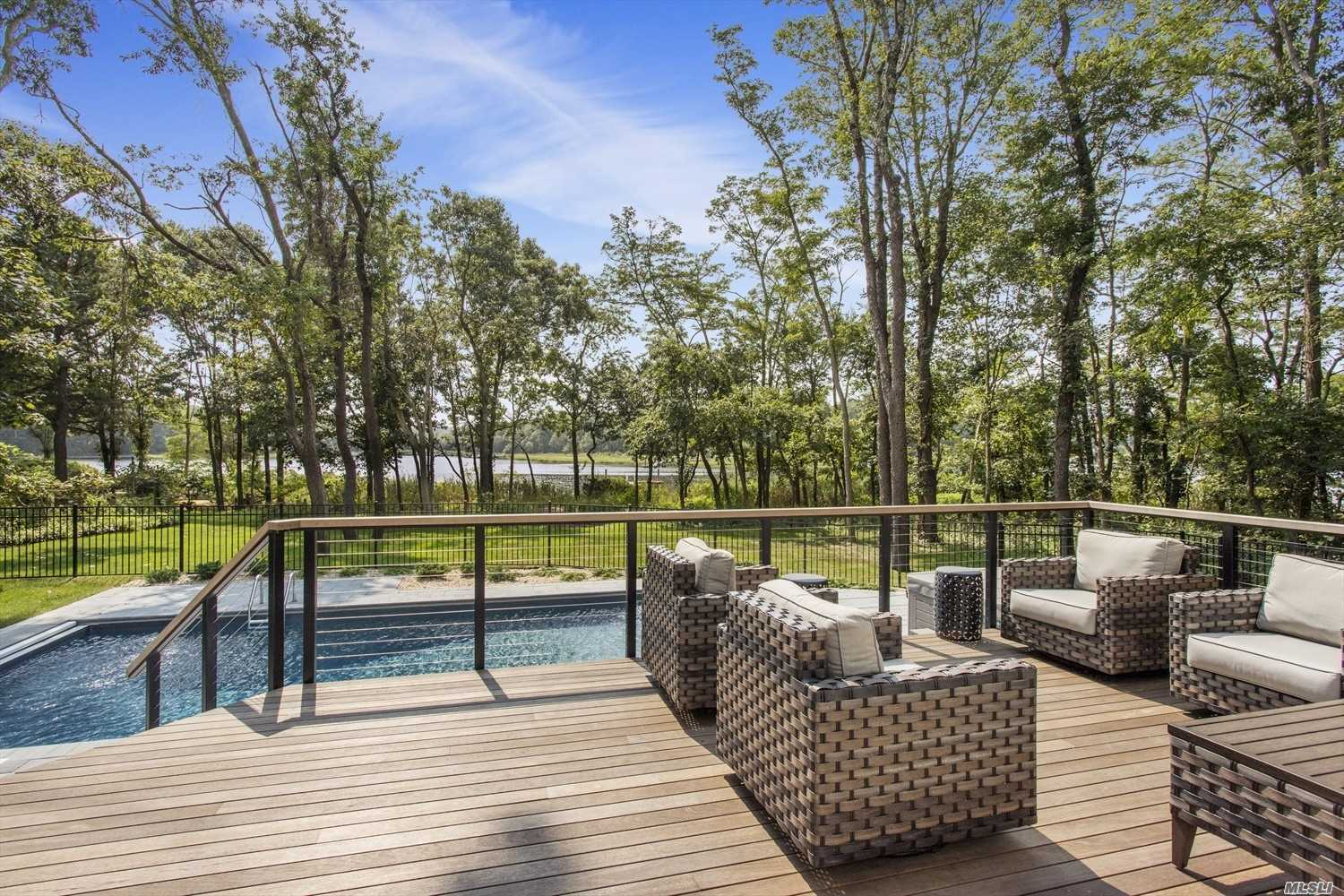 Modern Farmhouse W/Pool In Heart Of Mattituck! Nestled On Nearly Half An Acre W/Waterfront Views Sits This Newly-Constructed 5 Bed, 5 Bath Beauty, Boasting A Fully Finished Basement, Gourmet Kitchen, Spa-Like Master, Hot Tub, Sparkling 18X36 Pool, & Fenced Back Yard. Here You'll Enjoy A Gorgeous Mahogany Deck W/Remote-Control Awning, & An Expansive 75' Walkway Leading To A Floating Deep-Water Dock For Boating. Step Indoors To Find An Impressive 2-Story Floor Plan W/Ample Space To Host A Crowd.