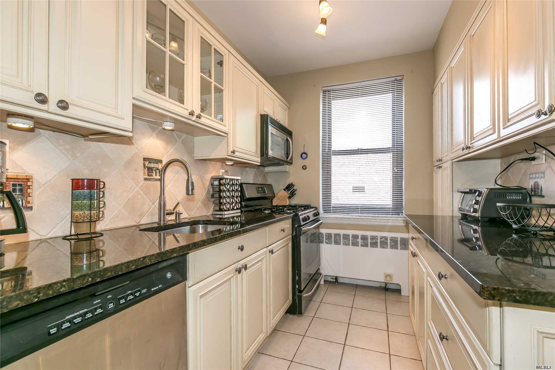True Gem In The Heart Of Town! Quiet Top Floor Corner Spacious 2 Bedroom All Renovated. Huge Liv Rm W/9' Ceilings, Large Custom Eat-In-Kitch W/Wood Cabs, Granite Counters & Ss Appliances. Separate Dining Area. Sunny King Sized Master Br With 2 Lge Closets, Renov Full Bath, Sunny Spacious 2nd Br, 3 A/C's & Ceiling Fans , Wood Floors, Fitted Closets. Elev Bldg, Garage Pkg W/L. Free Storage Cage, Cats Ok. Only 2 Short Blks To Train & Shops, Great Neck S. Schools.
