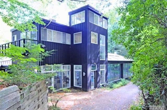 Unique contemporary home with 2.7 acres in serene setting with window walls facing forest in rear and lake in front. This 4, 858 sq. ft. home offers 5 oversized bedrooms, 6.5 baths, 2 fireplaces, indoor pool, patio and 2 decks. Close to LIRR & village. Laurel Hollow Beach & Mooring rights.