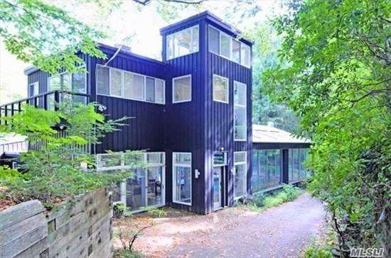 Rare opportunity to live in this cool luxurious home in private country setting with unique modern style and 2.7 acres of private woodland. This 4, 858 sq ft home offers 5 oversized BR, 6.5 Baths and 3 fire places with amazing lake views from floor to ceiling windows. Step out to courtyard patio from the rooms and from new kitchen with glass door. Indoor pool with roof that opens in summer. 2 Car garage. Close to LIRR & village. Laurel Hollow Beach & Mooring rights.