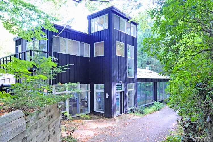 Unique contemporary home with 2.7 acres in serene setting with window walls facing forest in rear and lake in front. This 4, 858 sq. ft. home offers 5 oversized bedrooms, 6 baths, 3 fireplaces, indoor pool, patio and 2 decks. Close to LIRR & village. Laurel Hollow Beach & Mooring rights.