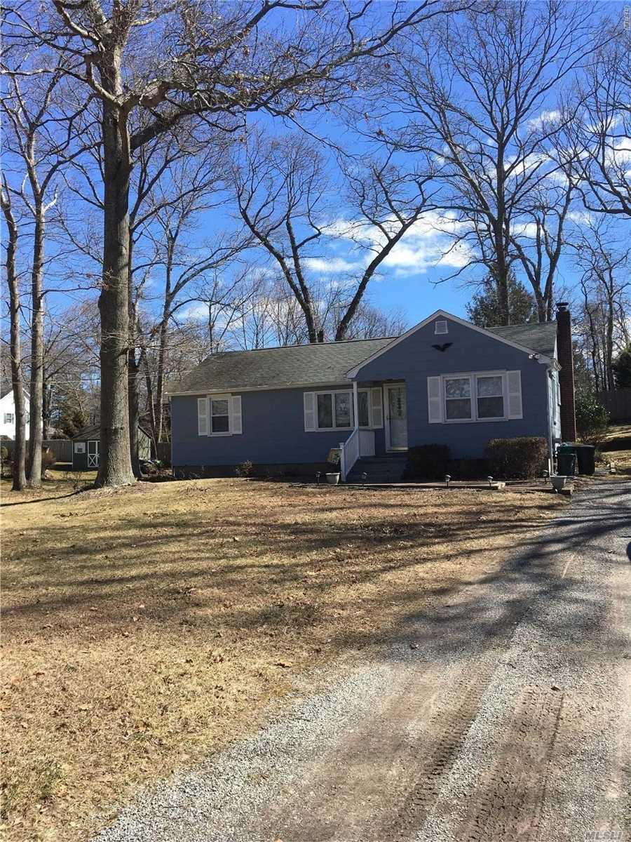 Blue three bedroom Ranch with gravel driveway