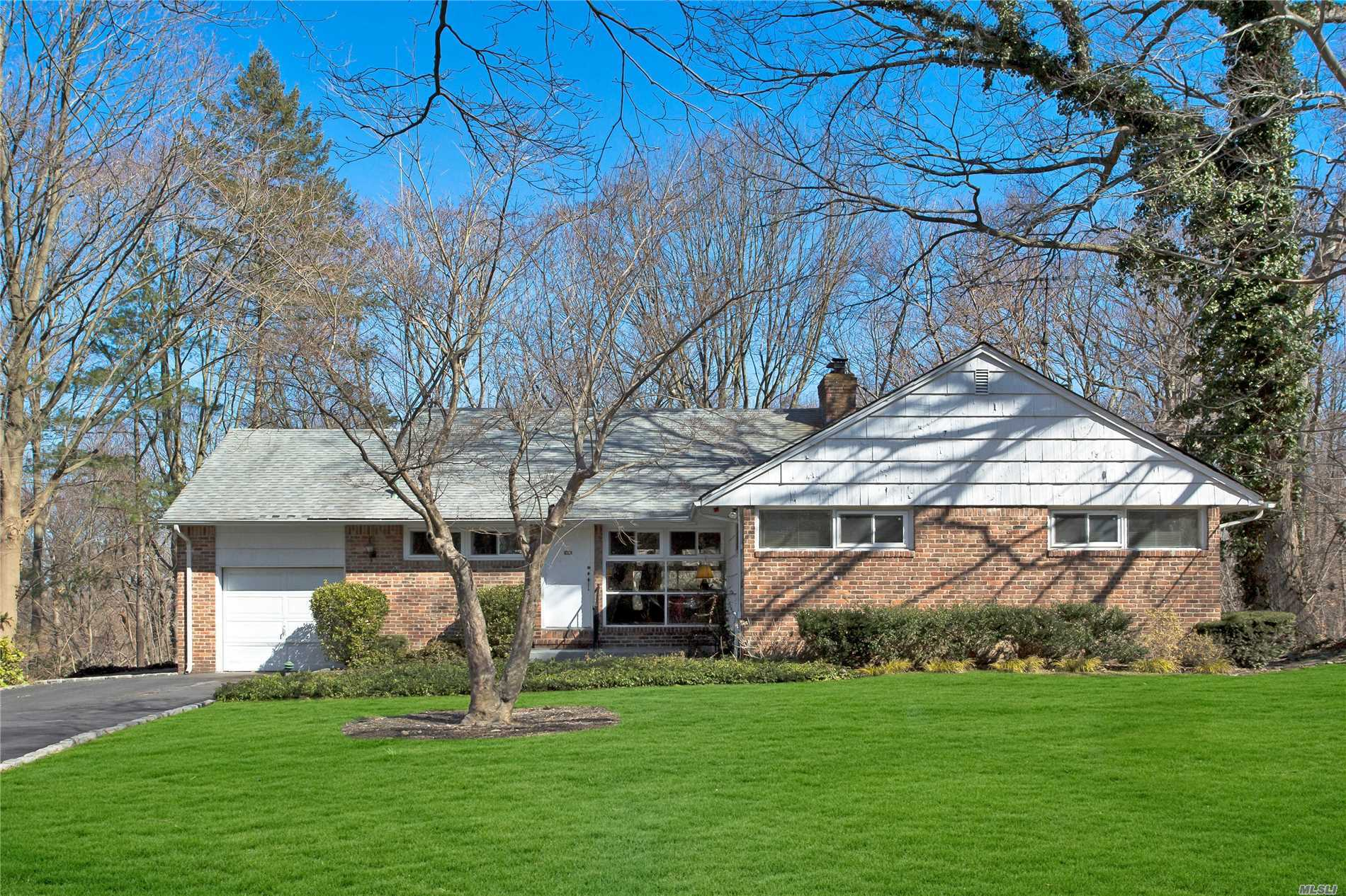 Roslyn Harbor Ranch with three bedrooms, two full baths, glass walled living room with fireplace and dining room overlooking picturesque one acre. Golden opportunity with amazing taxes