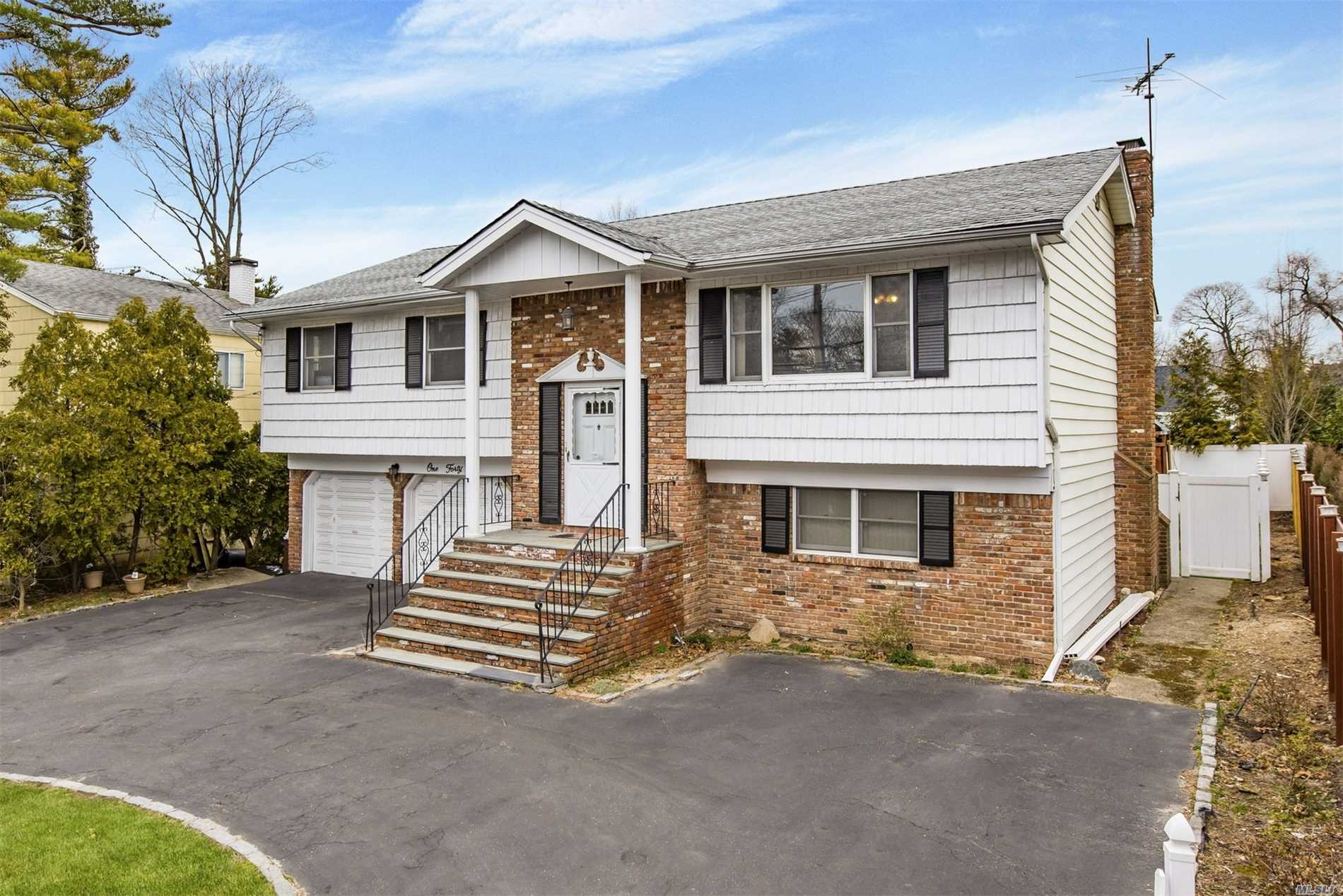 Light and spacious, well maintained raised ranch in the highly desirable Hewlett-Woodmere S.D. Newer roof, AC, baths, and upgraded kitchen. Wood floors throughout, fireplace in family room, two master bedrooms, outside deck off kitchen, huge garage, and parking for six cars. Possible mother/daughter with proper permits. 15 mins. to Kennedy Airport, 35 mins to Penn Station via LIRR.