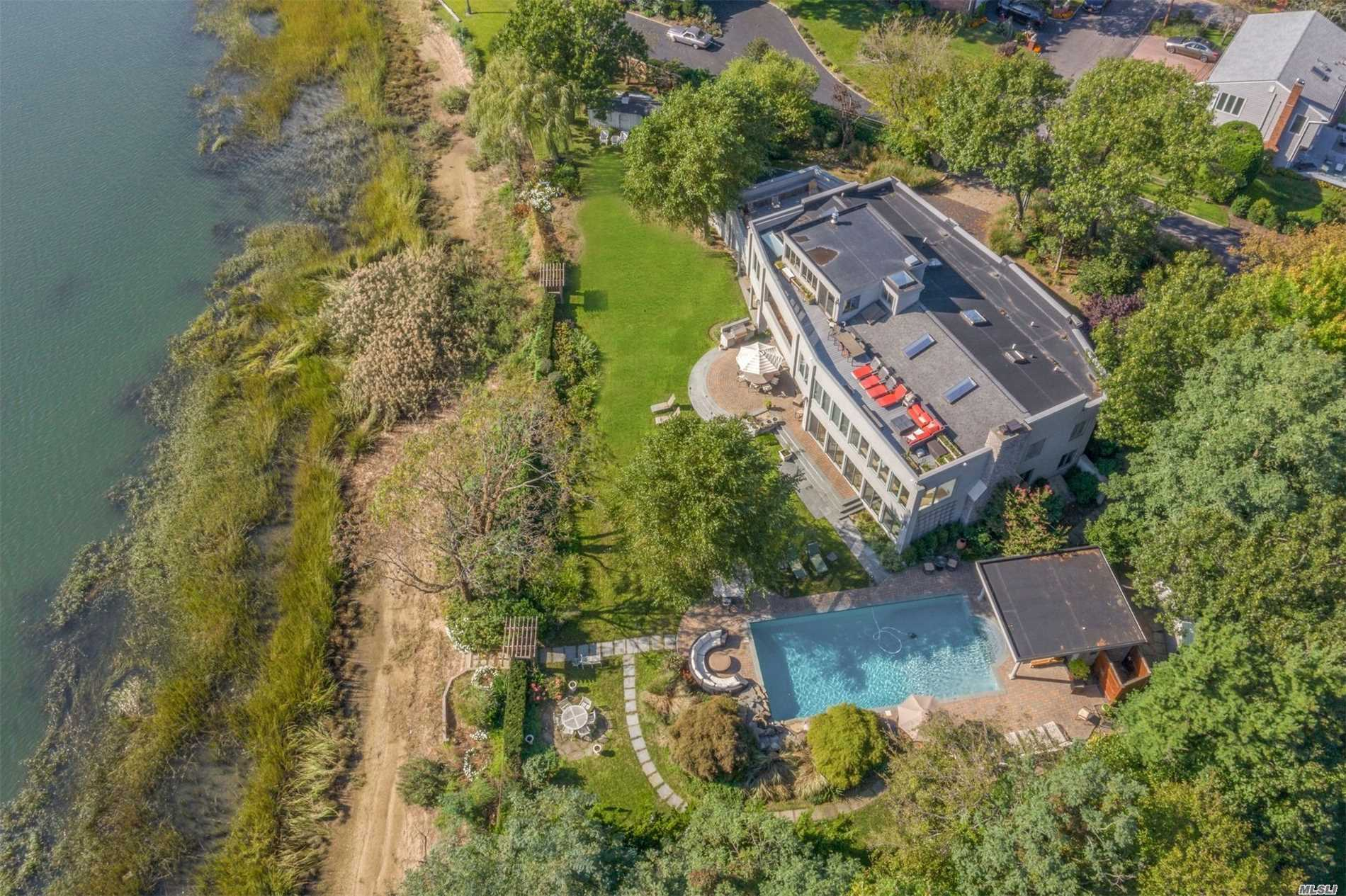 Impressive waterfront home with 290' on Mill Neck Bay. An entertainer's dream, this 5, 500 SF approx. Contemporary boasts panoramic water views from most rooms, an open sun-filled layout, soaring ceilings, indoor spa, multiple outdoor sun decks, and many high end custom details. Gorgeous heated pool with pool house on a beautifully manicured acre. Serene and private location, yet close to all.