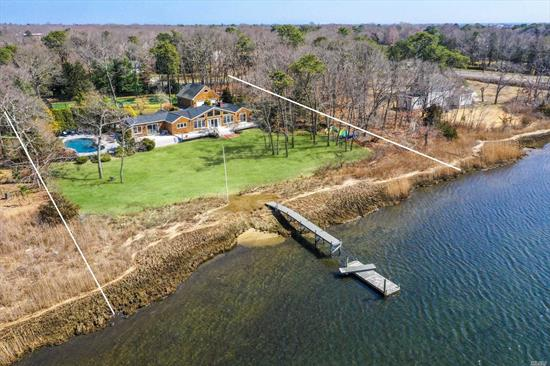Spectacular waterfront with beautiful private dock. Lovely 4-bedroom, 3-bath beach home set on 1.7 acres of lush landscaping with a gorgeous gunite pool/waterfall facing the wide stretch of water. All weather tennis court with a special soft-surface. Boat, kayak or canoe out to Quantuck Bay. An very beautiful Hampton Oasis. Use of Quogue Village beach. Very close to restaurants, resort shops, theaters, golf and more. This is Hamptons living at its best! Every Amenity that You Want or Need.