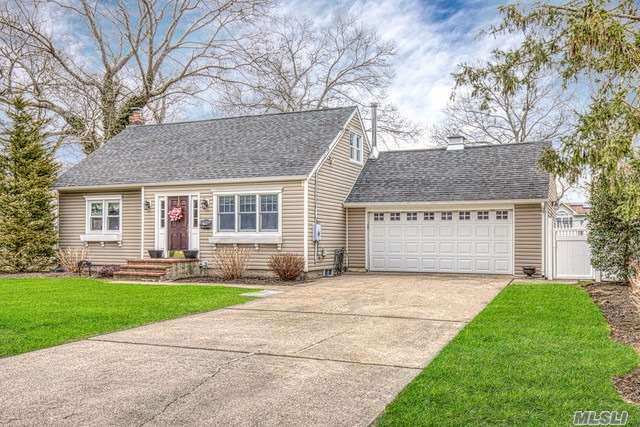 Lovely Cape, near schools. Lovingly maintained, inside and out! With gleaming wood floors throughout, New bathroom,  newer roof, furnace, and many newer windows, Expanded kitchen with wood burning stove and sliders leading to large deck. Large ground floor master bedroom, bright and sunny living room, with crown molding and rich detail. Full basement. Near schools!