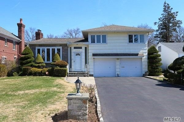 Beautiful sunny, charming & spacious 4 Br, 3 full bth, split level home on desirable block in Estates section. Expansive entrance leads to an open concept lr w/fireplace, fdr, lge elk w/ sliders to deck. Great for entertaining. Lower level has a family room w/separate entry, bedroom & access to 2 car garages. Plenty of room for nanny or extended family.Basement has a large den, laundry, full bth & storage. Lots of closets, large driveway (8cars), large yard, short distance to 2 train stations.