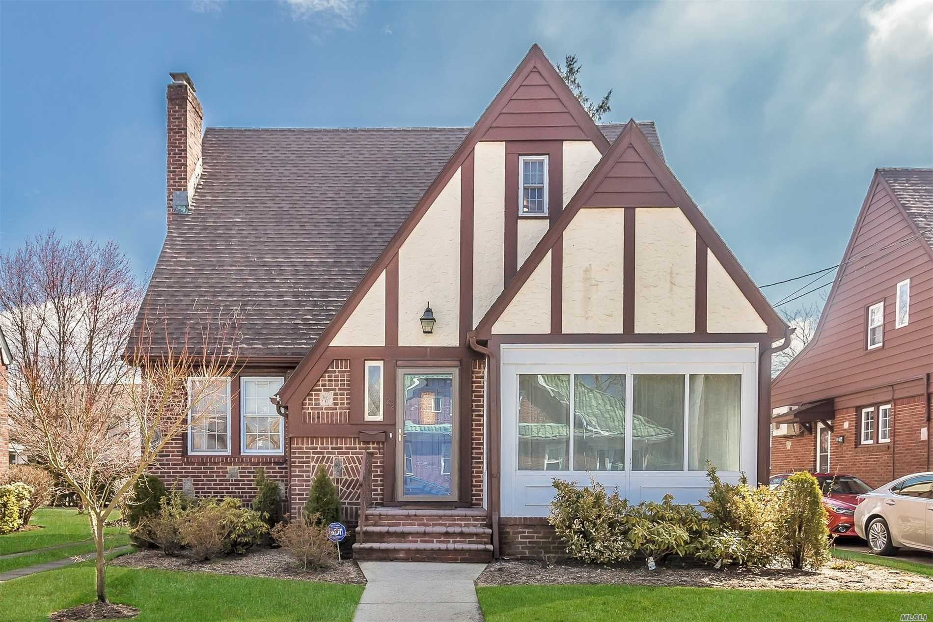 Stunning tudor with Manhattan vibe. Living room w/fireplace, true formal dining room, large eat in kitchen with island, enclosed porch,  1st floor bedroom with bath. Huge master bedroom, 2 new bathrooms, gas heat, ductless ac units, 2 car garage, close to malverne train for an easy commute into the city.