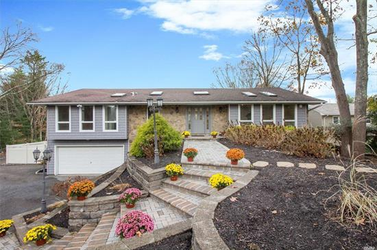 Smithtown Pines Ranch w/desirable Hauppauge SD! Beautiful home built on a hill w/ entry foyer,  Natural Light abounds, all new HW floors, custom white columns, LG open floor plan, new EIK w/ quartz counters, brand new deck off family rm, fireplace, MASTER BR with full bath and WIC, 3 other BRs, gorgeous view from formal dining room; freshly painted! Downstairs has summer KIT, LG window- brings in a lot of light, full bath, BR, laundry room, 2 car garage, extra parking, Walk in & fall in love!