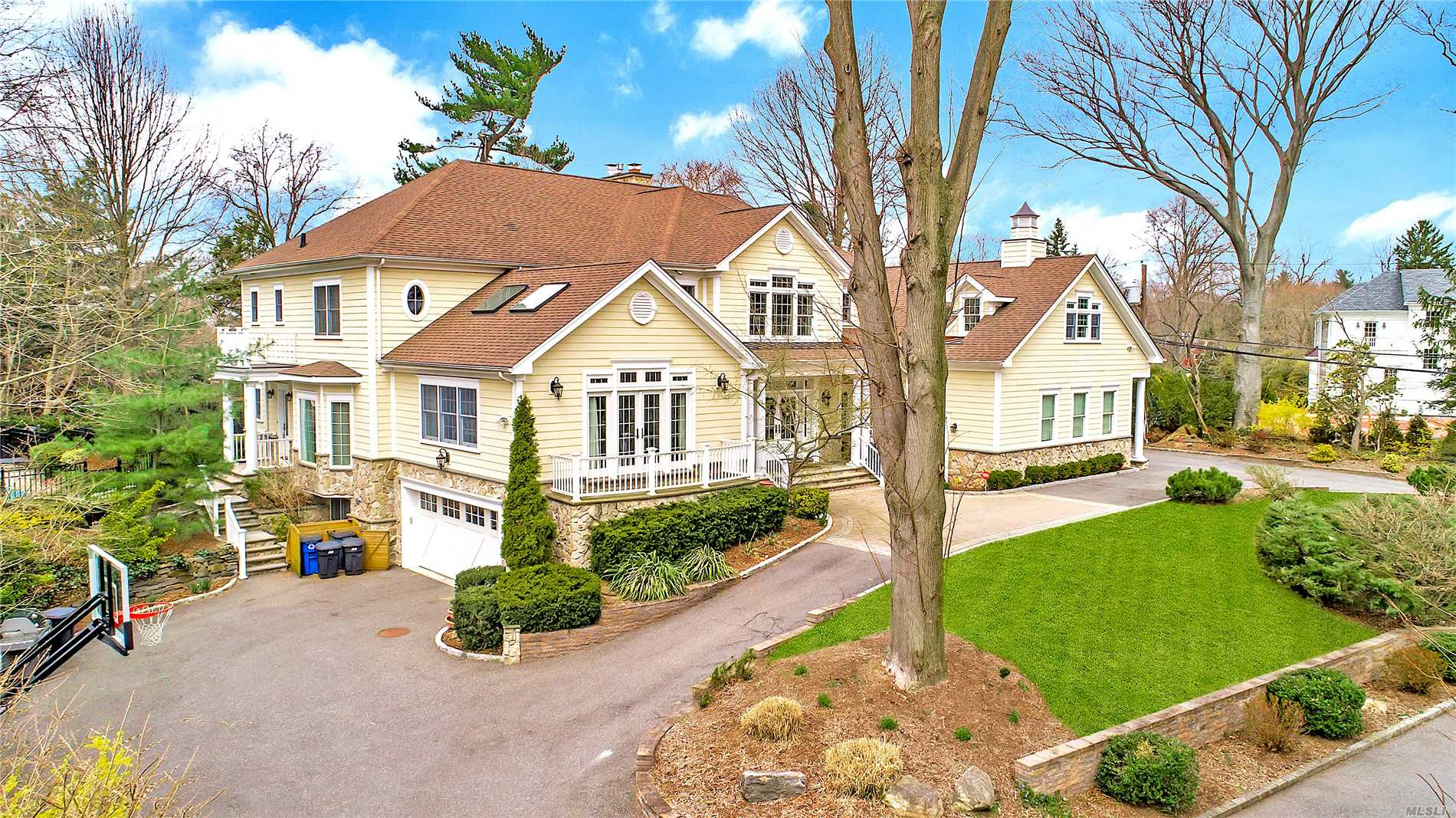 Welcome to this stunning stone and shingle colonial home situated on a shy acre of land in the heart of prestigious Plandome Manor. The residence, accessed down a long private driveway, features spectacular grounds which include a heated in-ground pool, a cabana, and ample open space.