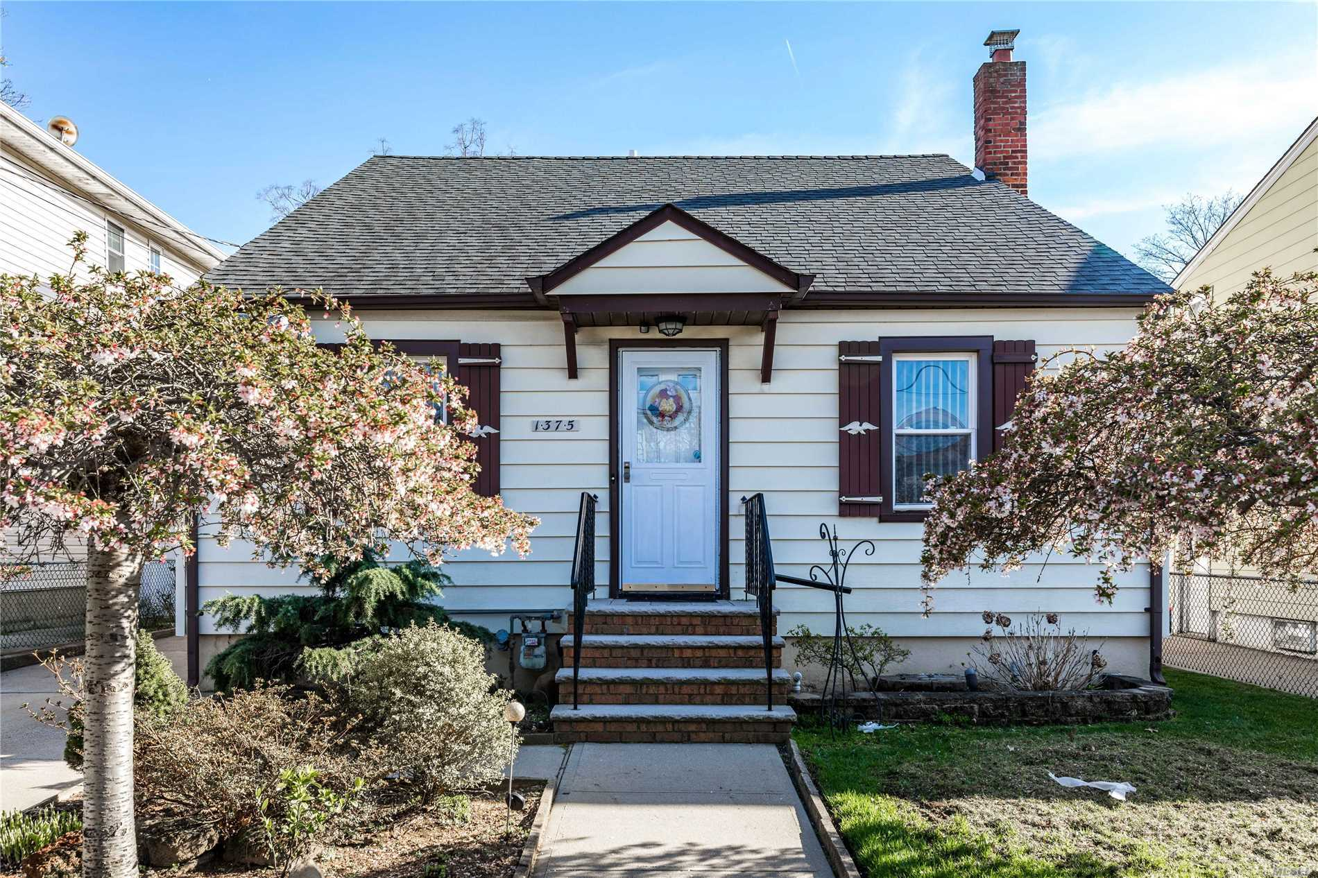 Elmont Home.....4 Bedroom 2 Full Bath EIK Dining Room Living Room Full Finished Basement with Outside Entrance Boiler and Roof only 4 years old Gas Cooking In Ground Sprinklers PVC Fence Garage Half Dormer Cape Cod Home!
