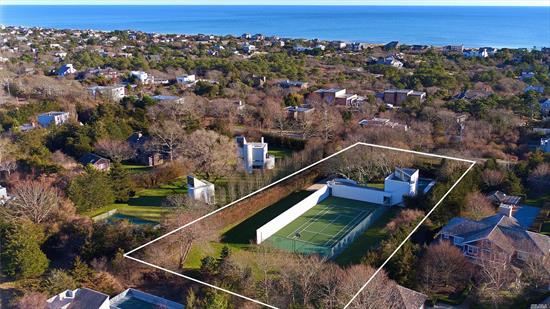 Here is a rare opportunity to own this widely publicized modern work of art. This is one of only two properties on Bluff Road with a grandfathered in tennis court on a one+/1 acre lot. The living area has a soaring double height ceiling with large windows on all sides providing plenty of sun.