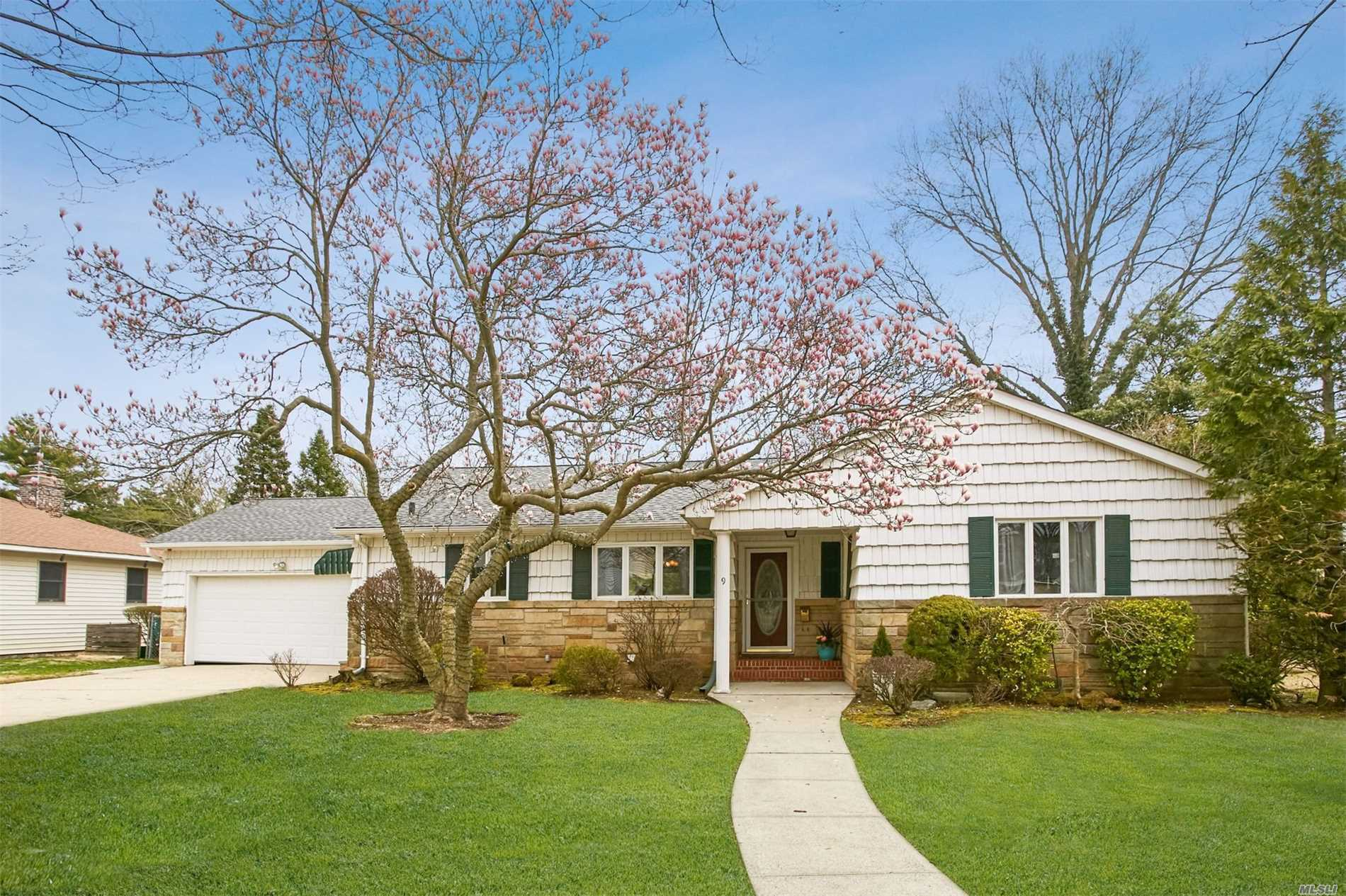 This style savvy home has an open & sun-lit layout sited mid-block with an expansive backyard convenient to the Stewart Manor LIRR Station. Living room has a vaulted ceiling with 2 skylights, sliders to a patio & a gas fireplace all open to dining room. There is a large granite EIK & SS appliances & a door directly to the side by side driveway & 2 car garage. The finished basement is huge with a recreation room & 2 finished rooms. Looking for easy living - this is a must see for you.
