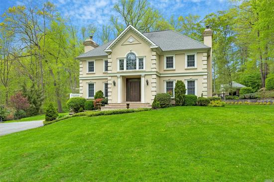 "Standing regally on a gentle hillside, this timeless stucco French Colonial, with coins, hip roof, domed chimneys, elegant moldings, and coat-of-arms, welcomes guests up a long, winding drive partially shaded by stately, towering oaks. Off a quiet cul-de-sac in Lattingtown, this magnificent two-acre mini-estate is carved out of pristine woodland and features sweeping emerald lawns, stone-tiered gardens, and an entertainer's-dream outdoor entertainment complex. An enthralling country-club ambiance carries on into the home's bright and spacious, four-bedroom, three-bath interior offering a casual elegance with easy flow from space to space, natural-tone hardwood floors, elegant millwork, large windows, French doors, a fabulous finished basement, and a huge unfinished attic with expansion possibilities. On the shores of Long Island Sound, Lattingtown is the northernmost part of a larger area, fanning out from the village of Locust Valley, that is referred to by many as ""Locust Valley,"" just as all seaside communities on Long Island's lower eastern peninsula are called ""the Hamptons."" Located less than 30 miles from Manhattan, it has in recent years become a closer and more appealing destination for a younger generation of successful New Yorkers to live.  It is known for its grand estates, scenic vistas, country and golf clubs, and its proximity to yacht clubs, fine dining, quaint shopping districts, private and public schools, and the Long Island Railroad.  Amidst serene gardens and rolling lawns with a backdrop of soaring trees, the rear property's resort-like retreat begins with an expansive rear granite patio, ideal for al fresco dining, that leads via a bluestone path through gated estate-fencing to an enchanting inground, Gunite, salt-water pool that has been recently renovated like new. Hidden pool equipment includes a brand-new filter system with a super-quiet, four-speed pump, salt cell, and existing heater. Upgraded electrical equipment comprises six Intellibrite LED pool lights with multi-color functions and software for manual or phone/tablet control of lights, pump, heater, and waterfalls. An expansive surround and patio are enhanced by a new blue-tile raised wall containing a triple waterfall. A brand-new pool house, designed, architecturally drawn, and built from the ground up, boasts central-air conditioning and heat for year-round enjoyment. A large great room contains a granite-topped kitchenette with center island, high-end refrigerator, freezer drawers, ice machine cabinet, and dishwasher. There is a full bath with a glass enclosed indoor shower plus an outdoor shower with its own brand-new septic system. A Nana window system opens the kitchen to a six-foot bar, with ample seating, in one of two raised verandas overlooking the pool. The interior begins with a two-story central foyer, with elegant staircase, extending through to kitchen and French doors accessing the rear deck. The living room is flooded with light through two six-over-nine front windows and French doors to a side balcony flanking a massive marble fireplace. The formal dining room opens through wide French doors to a versatile sitting room, with direct access to the kitchen, ideal for additional seating or buffet for large dinner parties. The sky-lit, vaulted-ceiling kitchen enjoys custom cabinetry with white marble countertop, high-end appliances, a farm sink overlooking the patio, a pantry, and a delightful breakfast area offering gorgeous vistas through a bay of six large windows. A hall off the foyer leads to a lovely marble full bath and a spacious study/family room with fireplace and French doors to the rear patio. This area could easily convert to a first-floor master suite if desired.  The second-floor master suite offers a large bedroom with ample closets and room for more, a gorgeous marble master bath with whirlpool tub and glass-enclosed shower, and access to a private balcony overlooking the foyer with Palladian window and two closets. Two additional bedrooms share an attractive hall bath. The fabulous finished basement is ideal for entertaining and has access to the driveway. It includes a great room with fireplace, game room, gym, bonus/sound room, bedroom, full bath, and access to the attached two-car garage. Offering the quintessence of ""Gold Coast"" luxury living, this exceptional pristine home is ready for you to make it your own Shangri-la."
