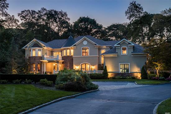If the cares of the world haven't left you as you wend your way along a private, third-mile, wooded drive, then this fairytale-like estate will complete the job. Like a castle in the woods, it greets you with a magnificent brick, stone, and stucco façade, a turret with steeple, arched windows, stone-like balustrades, an architectural roof resembling slate, and Brass Lions guarding entry to a large portico and patio. Standing majestically on 2.18-acres, this Continental-style abode enjoys a secluded and amazing rear property with endless areas for entertaining and pure enjoyment. An expansive bluestone patio extends the width of the house, from a shady veranda at one end, past an awning-covered outdoor kitchen replete with grill, granite bar, sink, griddle, refrigerators and more. Not far away, copper sculpted children sit atop a babbling waterfall, beckoning all to enjoy the inground, heated pool at their feet, slide down the water-park slide, or perhaps enjoy the adjoining spa with seating for a crowd.  As fabulous as its exterior delights are, this exceptional, 2006, custom-built, seven-bedroom, four-and-a-half-bath mansion is even more alluring. Entered through massive iron filigree-and-glass doors, the soaring two-story foyer creates a mesmerizing feeling that you are in a French-boutique hotel's courtyard. Overseen by windows and a Juliet balcony, this unique space features inlaid stone and marble radiant heated floors, exquisite moldings, and a graceful staircase with filigree balustrade winding up to the second-floor balcony. Beautifully designed for ease and comfort in entertaining, the main level features rich Brazilian cherry floors and gorgeous gas fireplaces in the formal living room and billiards room. The spectacular two-story den features a raised wood-burning fireplace, with access to the outdoor patio. The spacious eat-in kitchen is open to both the den through a large archway, and to the elegant formal dining room via a charming butler's pantry. Fr