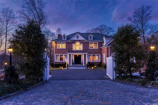"""Tucked away behind white gates on a magical and secluded property, this 2007 brick Georgian Colonial offers you an exceptional opportunity to own a magnificent and pristine six-bedroom, five-and-a-half-bath home in an enchanting setting and an ideal location. With all the grace and charm of a """"Golden Age"""" estate, this timeless beauty offers the comforts and amenities so desirable today. All this is off a winding wooded avenue in Roslyn Harbor, a small residential village overlooking the waters of Hempstead Harbor.  Originally a farming community, it was developed by wealthy New Yorkers into their summer estates.  Two of those properties remain today, the modern Engineer's Country Club and the William Cullen Bryant Preserve with the Nassau County Museum of Art.  Located just north of Roslyn Village, the area is convenient to shopping (including the Americana at Manhasset and the Miracle Mile), fine dining, golf, boating, fabulous parks, railway station, and major highways, putting it within about 45 minutes from Manhattan.  As you enter the courtyard of this beguiling residence, you may be intrigued by the sound of rushing water just out of sight. Pursuing your curiosity, you will find a waterfall cascading down several feet then tumbling along a stony creek bed to a wooded koi pond. There, you can enjoy a serene and quiet sitting area accessed from an enchanting stone bridal staircase. Perfectly built to transport you to a forest brook, these man-made wonders are just part of an acre of superbly designed landscaping with specimen trees and shrubs and a sweeping manicured lawn, all overlooked by an expansive raised stone patio. The house is equally impressive with its coined brick façade, slate-like architectural roof, and welcoming wide portico. Double doors open beneath a towering Palladian clerestory to an enthralling two-story center-hall foyer with graceful staircase and heated inlaid-marble floors. Coffered ceiling, fielded-panel walls, and stunning classic mol"""