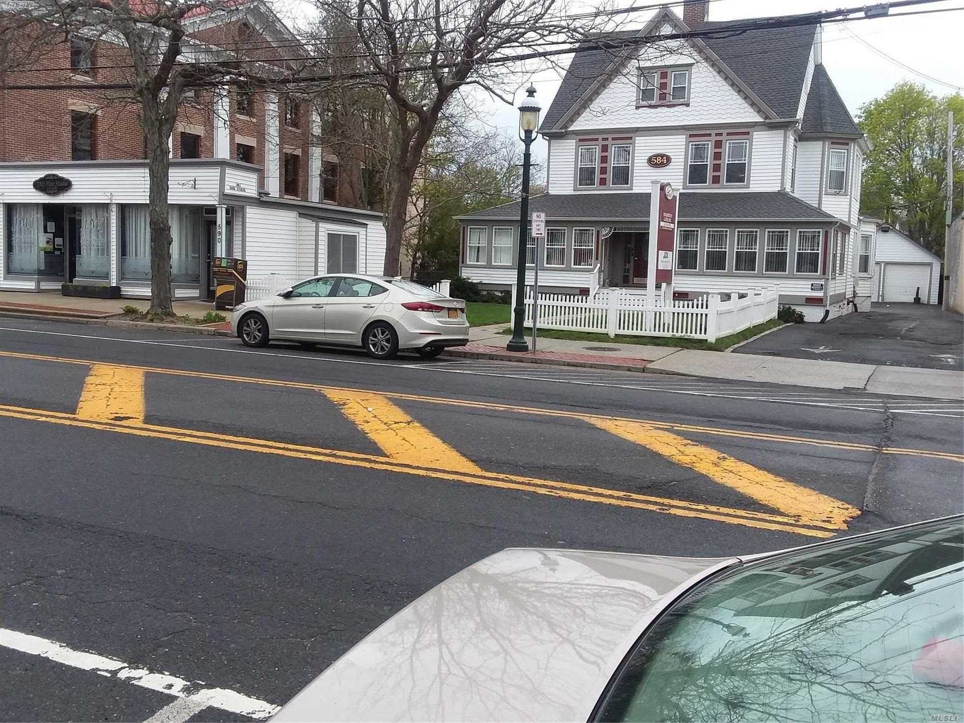 Beautiful Charming 3 story Victorian Colonial Building with 2 car detached garage, along with a one story storefront, under lease located in the heart of Islip Village