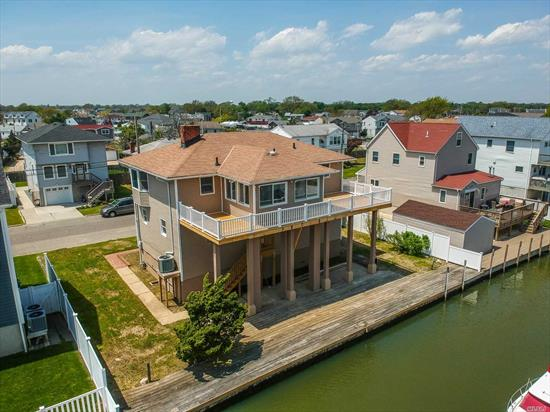 This spectacular Lifted Waterfront Hi Ranch is located minutes from the open bay. Sit on your deck and enjoy breathtaking views of the wide canal and open bay. Features include hardwood floors throughout, L/R w/gas fireplace. new kitchen boasts stainless appliances and quartz countertops. Family room w/bay views F/d & Living Rm, M/bedroom , Gas Heat, and much more. The 80 feet of bulkhead , customize downstairs bedroom,  jet skis, etc. Low Flood Insurance, Ask about our 12 Month Home Warranty