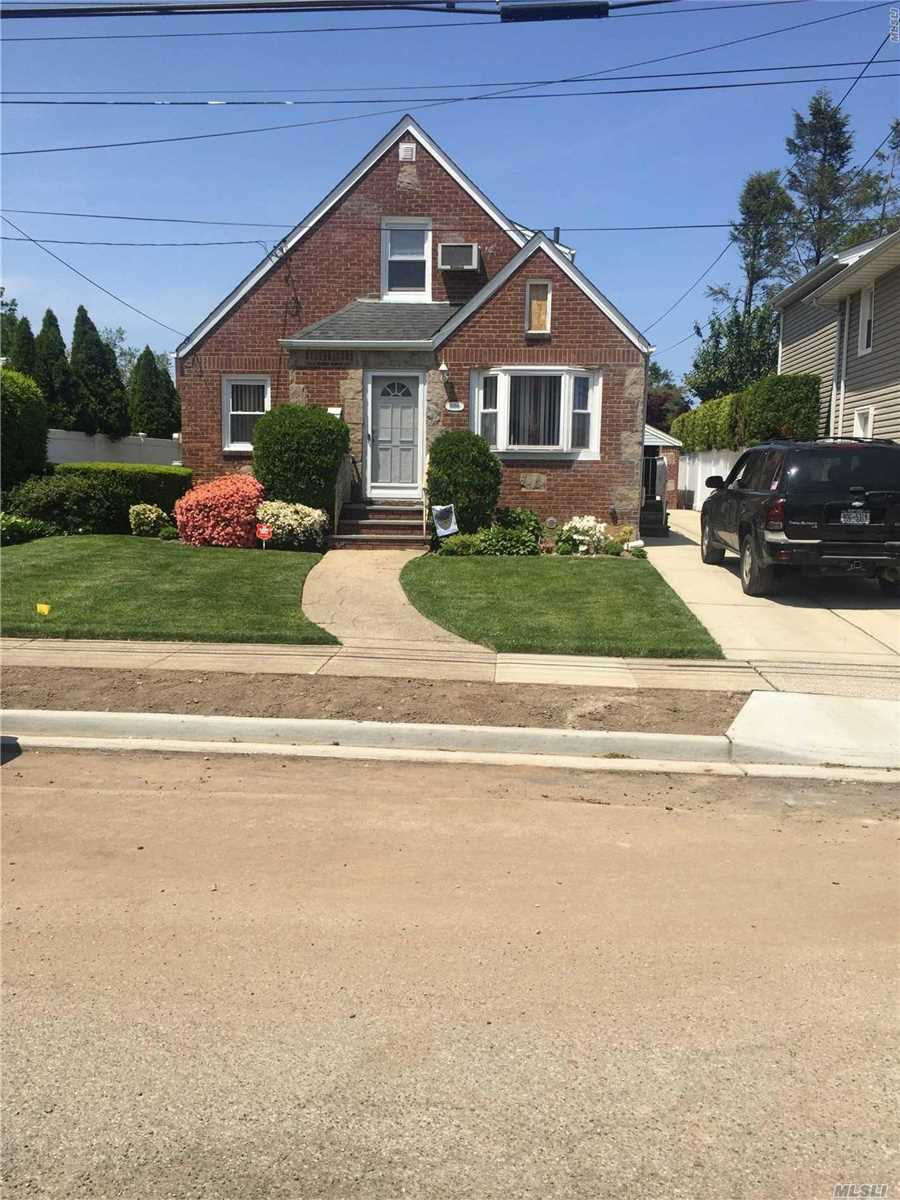 Brick cape in great condition with rear fla rm extension...Updated kitchen and baths..hardwood floors, new gas heating system new windows and driveway redone...4 zone ugs...central station, walk lirr, conv to all, tax grievance filed and transferrable
