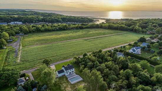 Mattituck, North Fork NEW construction MODERN FARMHOUSE w/pool and substantial terrace overlooking ag land and moments to fabulous Bailies Beach. Sleek design enhances the farm atmosphere of this spacious new home featuring foyer, pwdr rm, living room, formal dinning room, eik, den with fireplace, master suite w/bath, 3 additional bedrooms and bath. 2 car garage and sun soaked 1k+ sf terrace surrounding 20x40 inground, heated, swimming pool. Member Mattituck Park District.