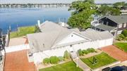 3058 square Foot Ranch Set On Baldwin Bay With Beautiful Sunset Views Features 700 Square Foot Attached Garage, 2 Private Driveways, In-Ground Gunite Pool, 100 Feet Of New Vinyl Bulkhead.
