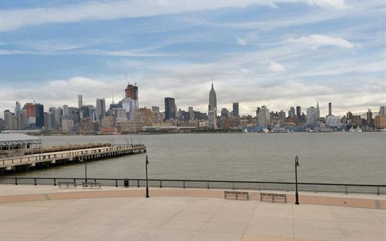 Maxwell Living doesn't get any better. 2703 SqFt triplex 2 bedroom plus den (easily used as a 3 Br) townhouse located across the street from the waterfront promenade. With 16 ft vaulted ceilings and floor to ceiling windows you will enjoy exquisite DIRECT VIEWS OF NYC and the Hudson River while your home gets flooded with natural light. Open style chef's kitchen features custom cabinets, granite counters and Bosch/Viking/SubZero stainless steel appliances. Oversized dining and living room with fireplace allows you the space that you deserve. 2ndlevel has a den that can be used a 3rd bedroom and is equipped with a full bath and wet bar. Top floor has 2 large master suites. Other great features include 4 full bathrooms, unparalleled storage and closets and indoor access to amenities. Community features 2 gyms, 2 pools, community room w theatre, 2 children's playroom and roof top gardens that are equipped with bbq's, tv and fireplace. Commuter's dream with the ferry and bus to NYC around the corner or take the private shuttle to the path. 1 indoor deeded spot included. Hoboken and Maxwell living at its best!!