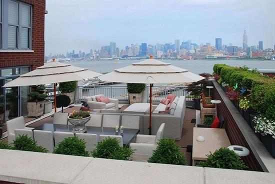 The ultimate in Luxury Living at Maxwell Place. 2 Br 2.5 bath with approx. 1000 SqFt private outdoor terrace with Direct NYC and Hudson River Views. This home spans from the NE corner to the SE corner and is unmatched in view and outdoor space by any other home in the Maxwell Community or Hoboken. Master Suite is located on NE corner with views of the GW Bridge and all of Midtown. Living, dining and sitting rooms all have direct Views of Manhattan. Chef's kitchen features granite counters, SS appliances, custom cabinets and custom lighting. Upgrades galore throughout the home include: Custom ceiling moldings, custom inlaid lights by Fios, Hunter Douglas electronic window treatments, Savant smart home technology system that operates, lights, window treatments and music, all closets have custom organizers, in wall speakers in every room. Landscaped roof terrace also has speakers, irrigation system and misting system. Community features 24 hr concierge, 2 pools, 2 gyms, community room w theatre and direct NYC views, landscaped roof terraces wth bbq's tv and fireplace, children's playroom. Commuter's dream with ferry around the corner or take the private shuttle to the path. Deeded parking included. Don't miss this once in a lifetime opportunity!
