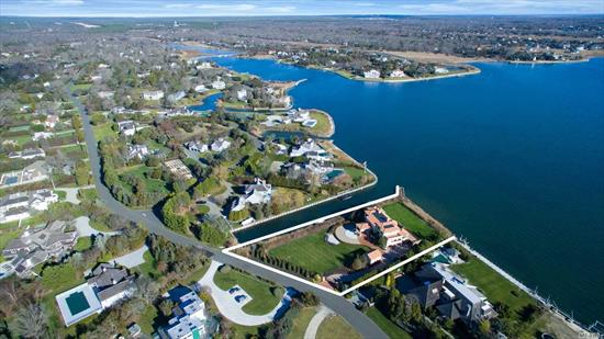 Trophy Bayfront Estate Compound. 5 Star sunrises from your custom pool and spa with over 600' feet of unobstructed open bayfront and adjacent deep-water canal. 1.6 acres of maturely crafted landscape nestled behind electronic gates. Enter the grand double foyer and be awestruck by the spellbinding views. Your oasis awaits you in this 4+ en-suite stunner replete w great room, formal dining, chef's kitchen, theater, billiard room, and gym. Guesthouse and endless amenities!
