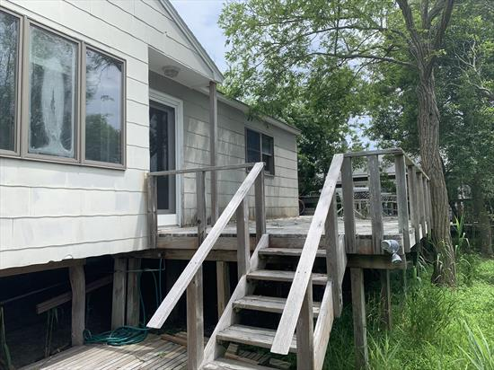 Amazing opportunity!  This charming, elevated 2 bedroom cottage sits on an oversized 75' X 100' lot.  Enjoy this affordable getaway as it is, or expand it to build your dream beach house.  Room for a pool!  Zoning allows for up to 2,625 square foot footprint for a new or expanded structure.  Great location halfway between the beach and town.     Updated bath and kitchen with stainless steel appliances.Endless possibilities!  Only 2 minutes to the beach!