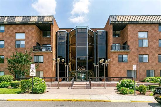 Bright and roomy Jr-4 unit converted into two bedrooms and 1.5 bath, LR/DR,  wood floors, EIK, ldry off of kitchen, CAC, indoor parking, facing back, in desireable condo bldg. of Cameo Plaza with Gym, 24 hr security, walk to town and LIRR