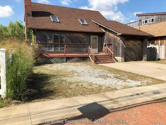 Waterfront cape with new bulkhead, wood floors and updated kitchen.