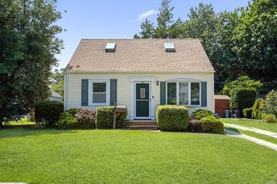 Beautiful Cape. Mod EIK w/pickled oak cabinets , granite counter, tile floor, stainless steel appliances. Mod Full bath w/ceramic tile. Den w/recessed lighting & sliding door to backyard. Beautiful Backyard completely private, enclosed w white PVC fencing and refreshing hot tube. Large Finished Storage Room in attic, carpeted w/heat and electric.. All windows double insulated windows, vinyl siding, new architectural roof w/ 2 skylights. Just a 6 minute walk to LIRR Gibson Station