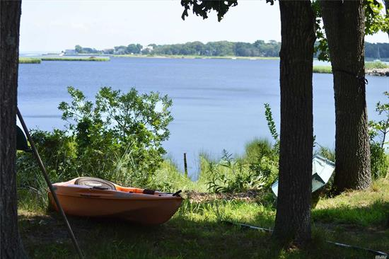 Nature Lover's Dream!! Beautiful and serene, this 1-acre plus open bay front property provides everything you could possibly want in a summer and/or year round home on the East End of Long Island. Featuring 4 BR & 2.5 BA, this spacious Colonial offers a stunning natural stone fireplace, huge Trex deck, large airy open floor plan, spacious bedrooms and water, water everywhere. Steps to your own private beach & dock. Minutes to everything the Hamptons has to offer. Best Waterfront Deal Around!