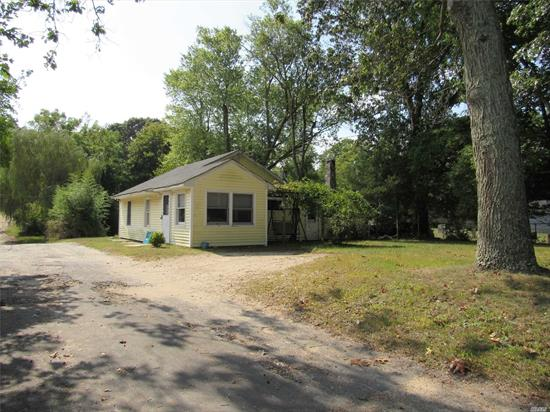 Plenty of privacy comes with this 1000+Sq.ft. starter home and 420 s.f barn on 1.4 acre. Surrounded on two sides by Suffolk County wooded Parkland, this home Includes 2 BR, LR w/fpl, kitchen, full bath, and enclosed porch. Sliders onto rear deck overlooking Koi pond and plenty of rear yard. Low taxes! Private Marina 1/3 mile. Rent a boat slip, and walk to bay at the end of the road. Close to shopping, ocean beaches, N.F. farms and vineyards. Please do not enter property without Agent!