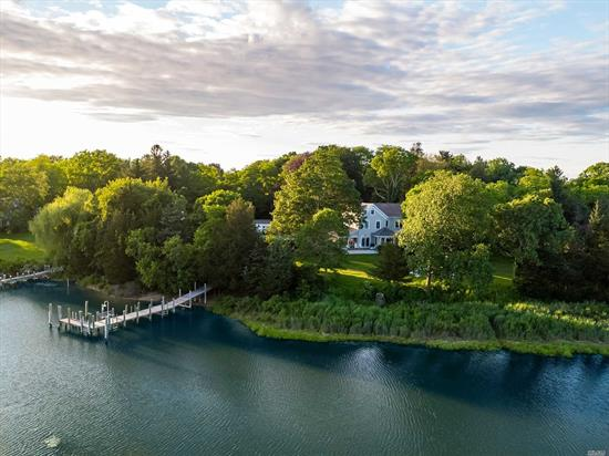 This magical waterfront homestead encompasses over 5 acres, 421 ft of water w. a dock and channels vacation vibes. 5+ BRs, 5.5 BAs, grand EIK w/ fpl, encl. porch, sun-room, LR w. a fpl and a partially fin basement. Step outside and experience the magic w/a heated salt water pool and spa, pool house w. BA and cabana changing area, 2 large barns, fire pits & outdoor seating throughout and a private deep water dock with access to the Bay. 3 separate build-able lots in total.