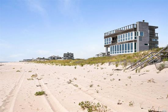 This property is spectacular, with 90 feet of ocean frontage, unobstructed views of Shinnecock Bay, and a chic, rooftop deck -complete with fireplace and hot tub. A unique setting, with preserved land to the north, the ocean to the south, and the fine amenities of Westhampton Beach and Quogue villages just a few miles away.The sophisticated home is poised right on the dune, with mesmerizing views from floor-to-ceiling windows. Open concept floor plan, with stunning finishes and a polished vib