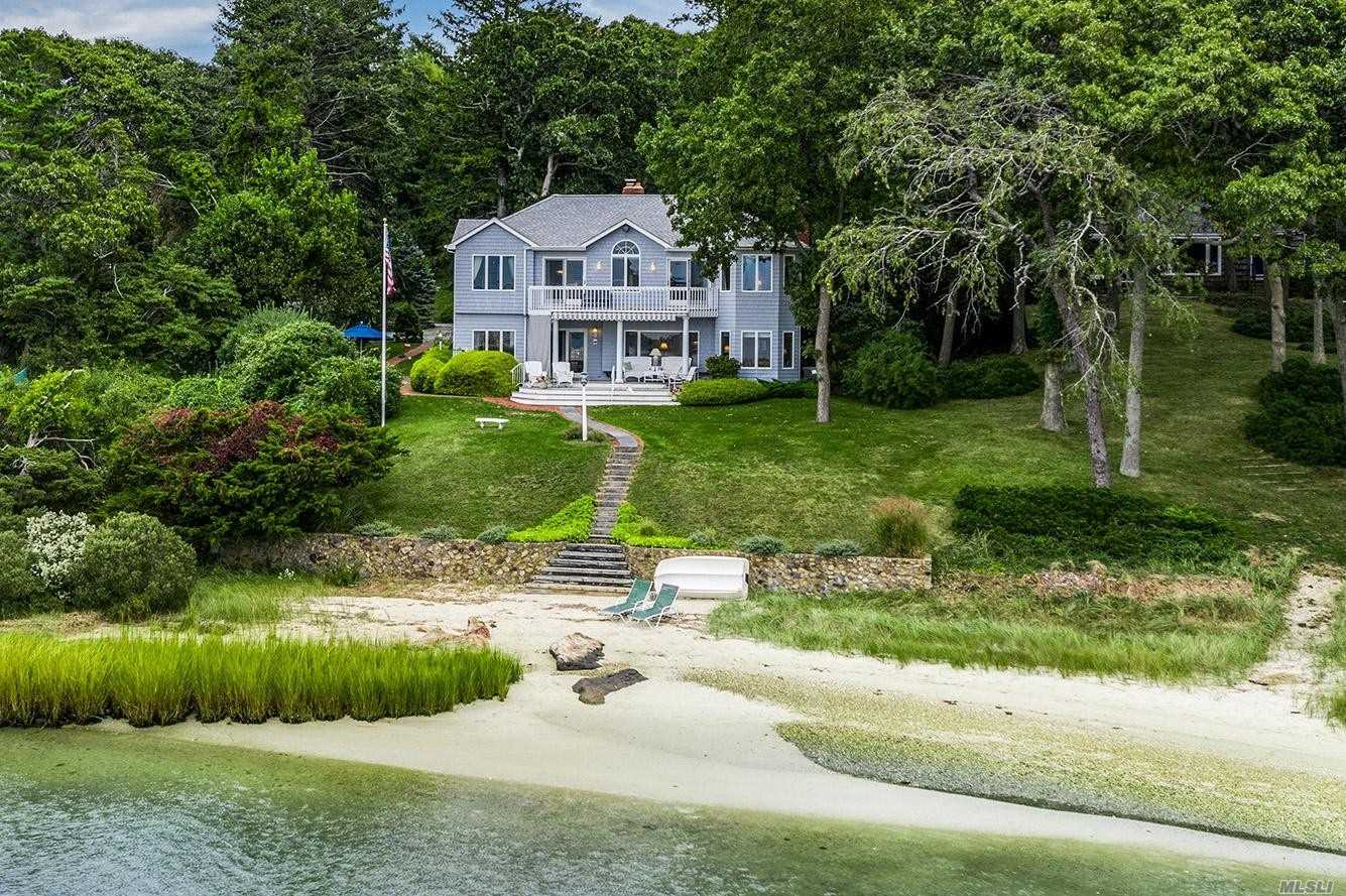 True Beach Front Home in Nassau Point overlooking Cutchogue Harbor & Robins Island w/Unparalleled Sunset Waterviews & Natural Storm Protection. This Cedar Shake Colonial Features Views Starting from the Entry way, Living Rm w/Frpl, Dining Rm W/Wd Flr, Eik has Newer Cabinets & Granite Counters, 1st Flr Br w/En Suite Bath, 2nd Flr Master Br w/Master Bth, WIC & Private Balcony. There is also a Sep Guest Cottage w/Living Rm, Kitchenette & Full Bath + a 2 Car Det Garage.